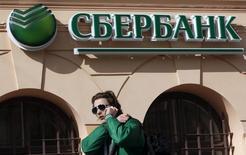 Мужчина проходит мимо отделения Сбербанка в Санкт-Петербурге 27 марта 2014 года. Крупнейший госбанк РФ Сбербанк в ответ на подозрения Киева в финансировании терроризма сообщил, что действует в строгом соответствии с законами и не знаком с претензиями Генпрокуратуры. REUTERS/Alexander Demianchuk