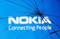 Разбитое стекло на фоне логотипа Nokia в Зенице 23 января 2014 года. Nokia приостанавливает продажи планшета Lumia 2520 в ряде европейских стран, в том числе в России, из-за неисправности в зарядном устройстве, из-за которой существует риск удара током. REUTERS/Dado Ruvic