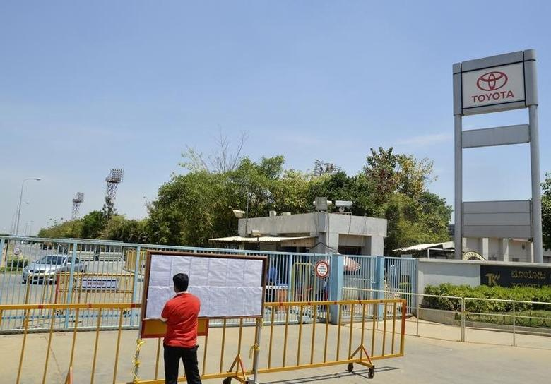 A man reads a notice installed on a barricade outside a closed plant of Toyota Motor Corp's India unit near Bangalore March 18, 2014. REUTERS/Stringer/Files