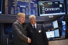 Le directeur général d'Omnicom John Wren (à gauche) et le président du directoire de Publicis Maurice Lévy l'été dernier à Wall Street après l'annonce de la fusion entre les deux groupes publicitaires. Le groupe américain s'est déclaré mardi dans l'incapacité de prédire quand serait finalisé ce projet de fusion du fait de retards dans les autorisations à ce mariage de 35,1 milliards de dollars (25,4 milliards d'euros) qui doit donner naissance au numéro un mondial de la publicité. /Photo prise le 29 juillet 2013/REUTERS/Shannon Stapleton