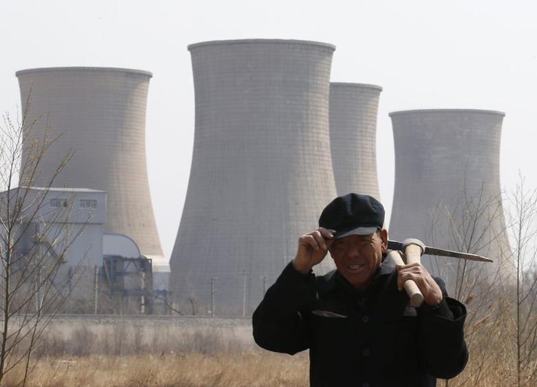 A worker walks past a steel factory in Beijing April 1, 2013. REUTERS/Kim Kyung-Hoon/Files