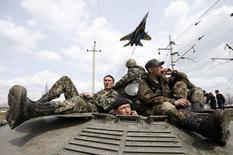 Истребитель пролетает над украинскими военными в Краматорске 16 апреля 2014 года. Власти Украины, пытающейся подавить вооружённые выступления пророссийских сепаратистов на востоке, уведомили в среду о планах провести в столице учения солдат и военной техники в ночь на выходной 1 мая. REUTERS/Marko Djurica