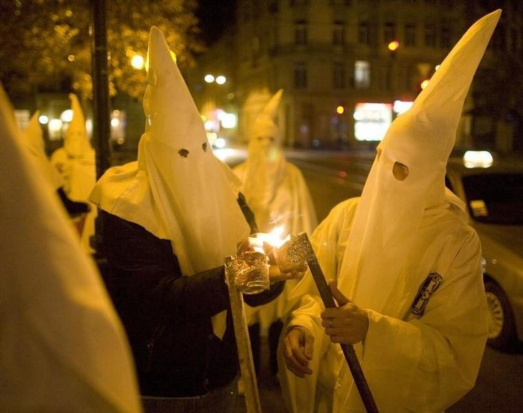 Supporters dressed as members of the Ku Klux Klan, using the occasion of Halloween to mask their faces from the police, light flares as they express anti-Semitic views in Lviv October 31, 2009,  REUTERS/Vasily Fedosenko/Files