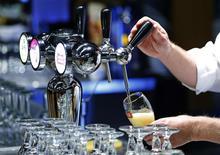 Бармен разливает пиво в стаканы перед встречей акционеров Anheuser-Busch InBev в Брюсселе 30 апреля 2014 года. Крупнейшая пивоваренная компания мира Anheuser-Busch InBev нарастила прибыль в первом квартале, однако рост оказался хуже ожиданий рынка из-за увеличения расходов на маркетинг в преддверии чемпионата мира по футболу. REUTERS/Yves Herman