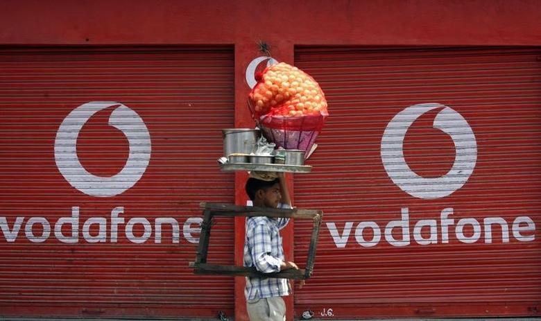 A vendor selling ''paani puri'', a traditional snack, walks past closed shops displaying an advertisement for Vodafone in Jammu May 22, 2012. REUTERS/Mukesh Gupta/Files