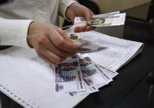 Кассир считает рубли в почтовом отделении в Симферополе 25 марта 2014 года. Рубль дорожал в первой половине четверга, отыгрывая заявления Путина на вчерашней встрече с ОБСЕ, но после отказа сепаратистов на востоке Украины переносить референдум растерял весь рост. REUTERS/Shamil Zhumatov