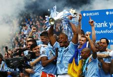 Manchester City's captain Vincent Kompany (C) celebrates with the English Premier League trophy following their soccer match against West Ham United at the Etihad Stadium in Manchester, northern England May 11, 2014. REUTERS/Darren Staples