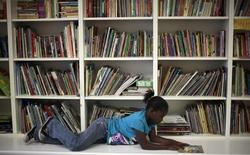 A homeless girl reads a book at a School on Wheels' after-school program in Los Angeles, February 9, 2012.  REUTERS/Lucy Nicholson
