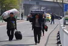 Migrant workers walk outside the South Railway Station in Urumqi, Xinjiang Uighur Autonomous Region May 2, 2014.   REUTERS/Petar Kujundzic