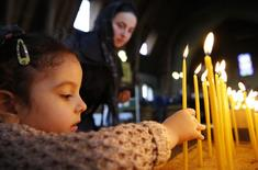 A child lights a candle to the deceased during a Saint John and Saint Alban the Protomartyr Romanian Orthodox service, at a church in Luton, southern England March 17, 2014.     REUTERS/Luke MacGregor