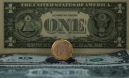 Монета евро и банкноты доллара США, Мадрид, 17 ноября 2011 года. Курс евро к доллару близок к пятинедельному минимуму, поскольку рынки все больше убеждаются, что Европейский центральный банк объявит о смягчении политики в июне. REUTERS/Sergio Perez