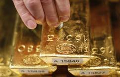 Работник немецкого ЦБ тестирует слиток золота с помощью ультразвукового аппарата на пресс-конференции во Франкфурте-на-Майне 16 января 2013 года. Цены на золото снижаются, но держатся выше $1.300 за унцию за счет напряженной ситуации на Украине и технических покупок. REUTERS/Lisi Niesner