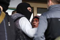 """Мужчина, которого пророссийские демонстранты назвали провокатором, у административного здания в Донецке 4 мая 2014 года. Наблюдатели ООН назвали пугающей ситуацию с соблюдением прав человека на востоке Украины и опасаются серьезных проблем в Крыму, сообщила верховный комиссар ООН по правам человека Нави Пиллэй, представляя доклад, который Москва заклеймила как """"вопиющий пример необъективности"""". REUTERS/Marko Djurica"""