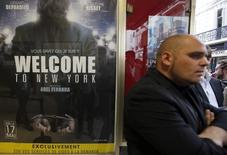 """A man stands next to a poster of the film """"Welcome to New York"""" directed by Abel Ferrara at a movie theatre ahead of a premiere screening during the 67th Cannes Film Festival in Cannes May 17, 2014.   REUTERS/Eric Gaillard"""
