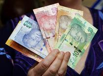 The hand of South African Reserve Bank Governor Gill Marcus is seen holding South Africa's  rand banknotes - which feature an image of former president Nelson Mandela on the front . REUTERS/Siphiwe Sibeko
