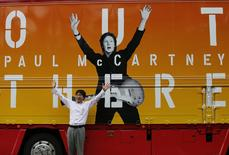 """A man poses for a photo in front of a truck with an advertisement for singer Paul McCartney's """"Out There"""" tour, after the cancellation of McCartney's concert at the Nippon Budokan in Tokyo May 20, 2014. REUTERS/Issei Kato"""
