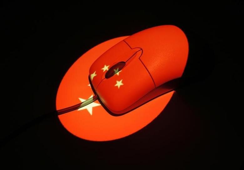 A computer mouse is illuminated by a projection of a Chinese flag in this photo illustration October 1, 2013.  REUTERS/Tim Wimborne/Files