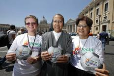 "Nuns Gabriella Bottani (L), Estrella Castalone (C) and Carmen Sammut hold the logo of an international campaign called ""Play in Favour of Life-Denounce Human Trafficking,"" on the risks they say will be associated with the June-July games, as they pose in front of Saint Peter's basilica in Rome May 20 2014.  REUTERS/Tony Gentile"