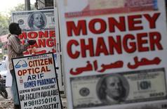 Мужчина просит милостыню у пункта обмена валюты в Дели 21 августа 2013 года. Курс доллара к иене близок к минимуму 3,5 месяцев за счет снижения доходности американских облигаций и накануне выступления главы Банка Японии. REUTERS/Adnan Abidi