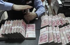 Работник банковского отделения в Хэфэе считает юани, 21 января 2013 года. Китай позволит десяти местным администрациям размещать муниципальные облигации в рамках эксперимента по приведению в порядок бюджетов, что станет поворотным моментом для решения проблемы госдолга страны в размере $3 триллионов. REUTERS/Stringer