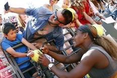 Serena Williams poses for a selfie with a supporter as she signs on a ball, after winning the women's singles final match against Sara Errani of Italy, at the Rome Masters tennis tournament May 18, 2014.  REUTERS/Giampiero Sposito