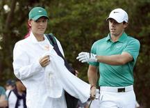 Tennis player Caroline Wozniacki of Denmark (L) works as the caddie for her boyfriend, Northern Ireland's Rory McIlroy, during the Par 3 Contest ahead of the Masters golf tournament at the Augusta National Golf Club in Augusta, Georgia April 9, 2014.   REUTERS/Mike Segar