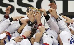 Игроки сборной России держат кубок чемпионов мира в Минске 25 мая 2014 года. Российская сборная по хоккею выиграла в воскресенье четвертый за последние семь лет чемпионат мира, частично реабилитировавшись за февральскую неудачу на домашней Олимпиаде в Сочи. REUTERS/Alexander Demianchuk
