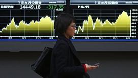 Женщина проходит мимо табло с котировками индекса Nikkei и иены в Токио 20 февраля 2014 года. Азиатские фондовые рынки завершили торги понедельника разнонаправленно под влиянием отдельных отраслей. REUTERS/Yuya Shino