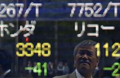 A man is reflected on an electronic stock quotation board outside a brokerage in Tokyo May 16, 2014. REUTERS/Yuya Shino