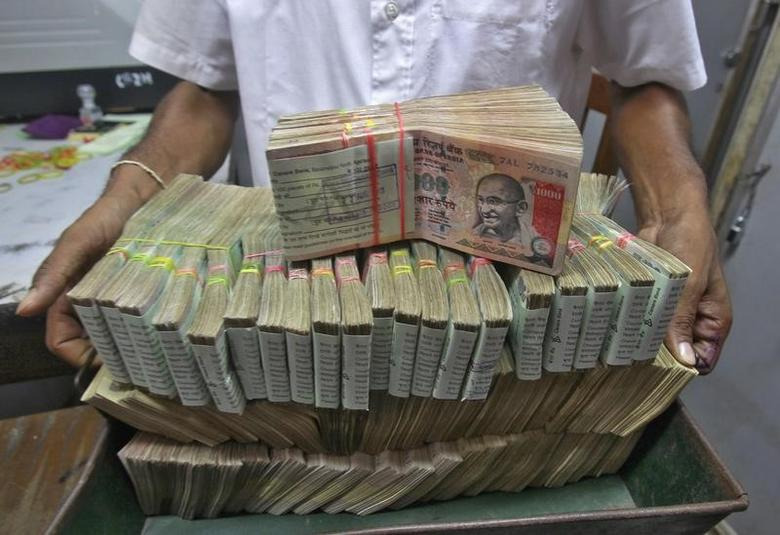An employee poses with the bundles of rupee notes inside a bank in Agartala, August 22, 2013. REUTERS/Jayanta Dey/Files