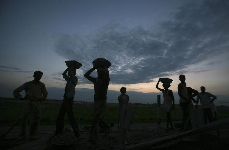 Labourers are silhouetted against the setting sun as they work at a road construction site in Greater Noida on the outskirts of New Delhi August 15, 2012. REUTERS/Parivartan Sharma/Files