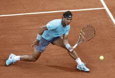 Rafael Nadal of Spain reaches out to return a forehand to Dominic Thiem of Austria during their men's singles match at the French Open tennis tournament at the Roland Garros stadium in Paris May 29, 2014.    REUTERS/Jean-Paul Pelissier