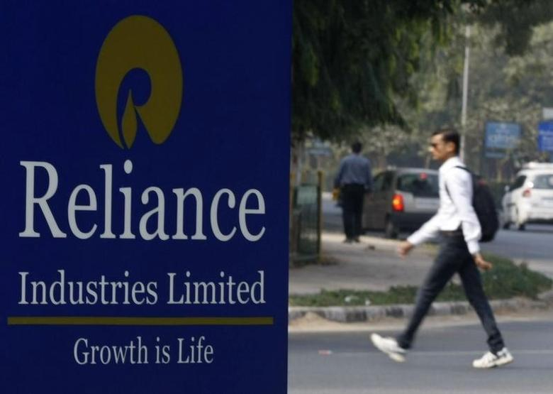 A man walks past a Reliance Industries Limited sign board installed on a road divider in Gandhinagar January 17, 2014. REUTERS/Amit Dave/Files