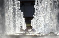 Люди среди фонтанов в Москве 28 июля 2011 года. Выходные принесут в Москву потепление, ожидают синоптики. REUTERS/Nikolay Korchekov