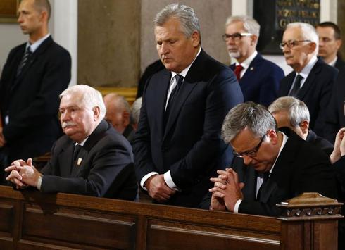 Poland's Walesa kneels in prayer at funeral mass for former foe Jaruzelski
