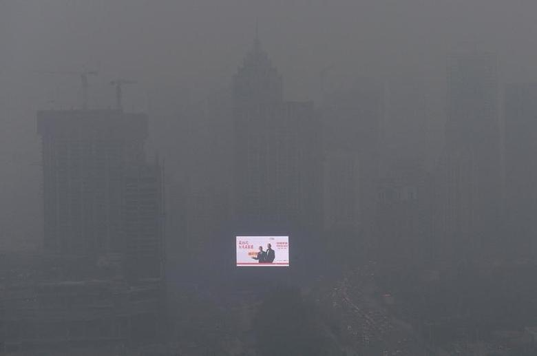 An electronic screen is seen on a building amid heavy smog in Shenyang, Liaoning province October 28, 2013. REUTERS/Stringer/Files