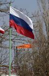 Российский флаг на фоне газового факела в Крыму 9 апреля 2014 года. Украина надеется завершить на этой неделе переговоры с Россией о цене на газ, но если это не удастся - переведёт разбирательство в Стокгольмский арбитраж, сказал премьер Украины Арсений Яценюк, выступая во вторник перед парламентом. REUTERS/Stringer