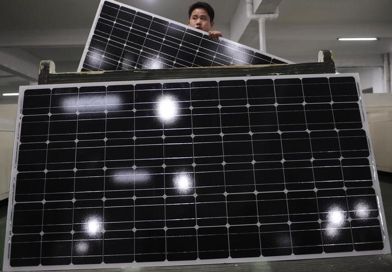 An employee carries a solar panel as he works at a production line at a solar company workshop in Yongkang, Zhejiang province February 23, 2012. REUTERS/Stringer/Files