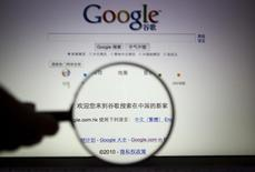 A person poses with a magnifying glass in front of a Google search page in this illustrative photograph taken in Shanghai March 23, 2010. REUTERS/Stringer