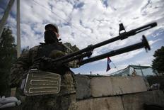Membro de milícia pró-Rússia monta guarda em um posto de controle na cidade de Slaviansk, leste da Ucrânia. As forças do governo ucraniano lutavam contra os separatistas com artilharia e armas automáticas nesta quarta-feira no segundo dia consecutivo de conflitos em torno da cidade oriental de Slaviansk, o que obrigou muitos moradores assustados a fugirem. 24/05/2014. REUTERS/Maxim Zmeyev