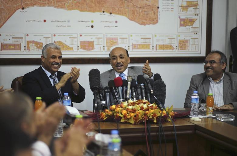 Palestinian Minister of Housing and Public Works Mufeed Al-Hassayna (C) gestures as he sits next to former Hamas government Minister of Housing Youssef Graze (L) during office handover ceremony in Gaza City June 4, 2014. REUTERS/Mohammed Salem