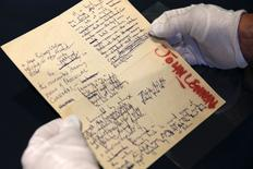 A Sotheby's employee handles a typescript signed by John Lennon during the press preview of a collection of Lennon's original drawings and manuscripts from 1964-65 at Sotheby's in New York May 29, 2014. REUTERS/Shannon Stapleton
