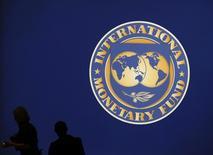 Посетители у логотипа МВФ в Токио 10 октября 2012 года. Международный валютный фонд сократил прогноз экономического роста Китая на 2015 год примерно до 7 процентов, но призвал власти избегать новых стимулирующих мер и сосредоточиться на снижении финансовых рисков. REUTERS/Kim Kyung-Hoon