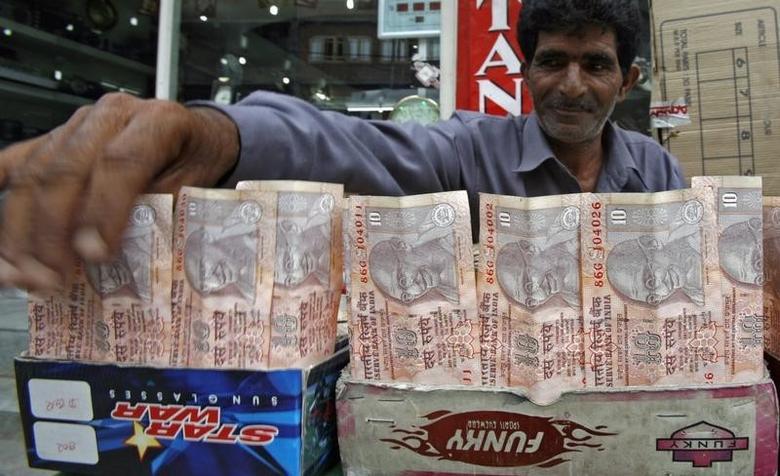 A Kashmiri money changer Nissar Ahmad displays rupees in Srinagar July 21, 2008. REUTERS/Fayaz Kabli/Files