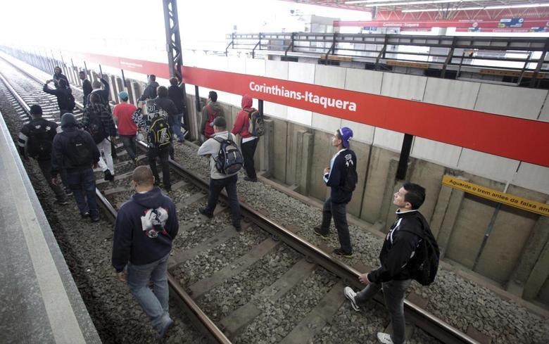 Commuters walk on railroads tracks at Itaquera subway station in Sao Paulo June 5, 2014. REUTERS/Chico Ferreira