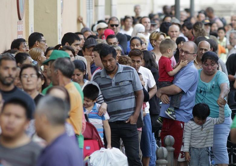 People line up to receive bags of food delivered by volunteers of the Banco de Alimentos (Food Bank) in Valencia, June 3, 2014. REUTERS/Heino Kalis