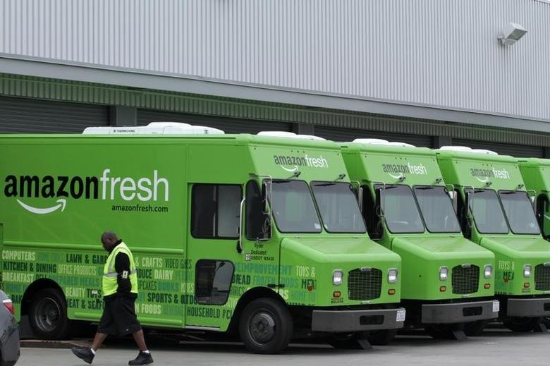 A worker walks past Amazon Fresh delivery vans parked at an Amazon Fresh warehouse in Inglewood, California, June 14, 2013. REUTERS/Jonathan Alcorn/Files