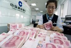 A clerk counts Chinese 100 yuan banknotes at a branch of China Construction Bank in Hai'an, Jiangsu province June 10, 2014. REUTERS/China Daily