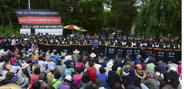 South Korean policemen stand guard in front of the main gate of the Evangelical Baptist Church premises, as church believers sit in front of the police barricade, in Anseong June 11, 2014. REUTERS/Kim Young-jin/News1
