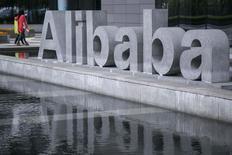 En la imagen de archivo, dos personas caminan junto al logo de Alibaba en la sede de la empresa en Hangzhou, en la provincia de Zhejiang, el 23 de abril de 2014. La empresa china de comercio electrónico Alibaba presentó el miércoles su primera tienda online dirigida al consumidor en Estados Unidos, lo que supone enfrentarse a Amazon.com y eBay en su propia casa. REUTERS/Chance Chan